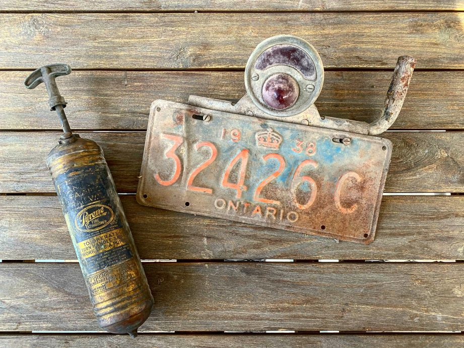 An old licence plate on a wooden table.