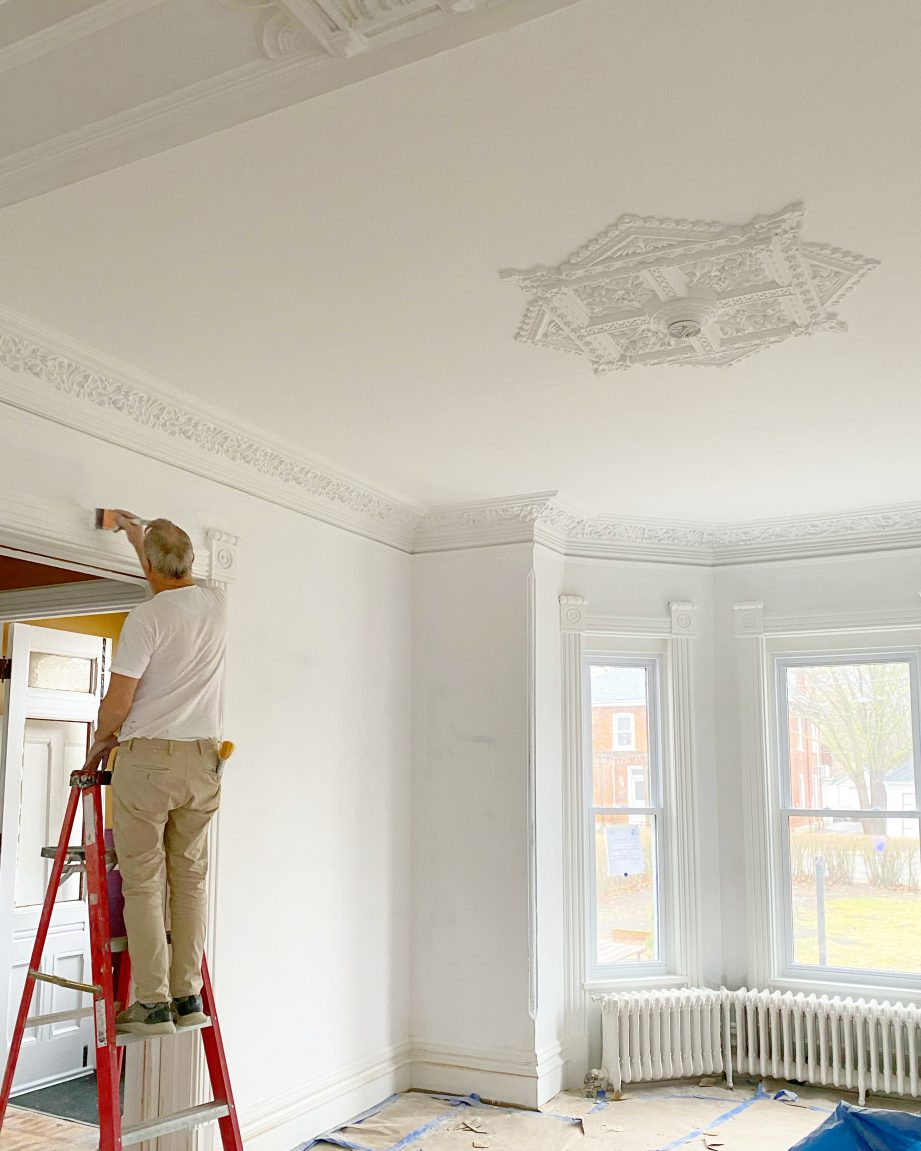 A person on a ladder painting a white room.
