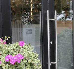 A black door with silver handle and flowers out front.