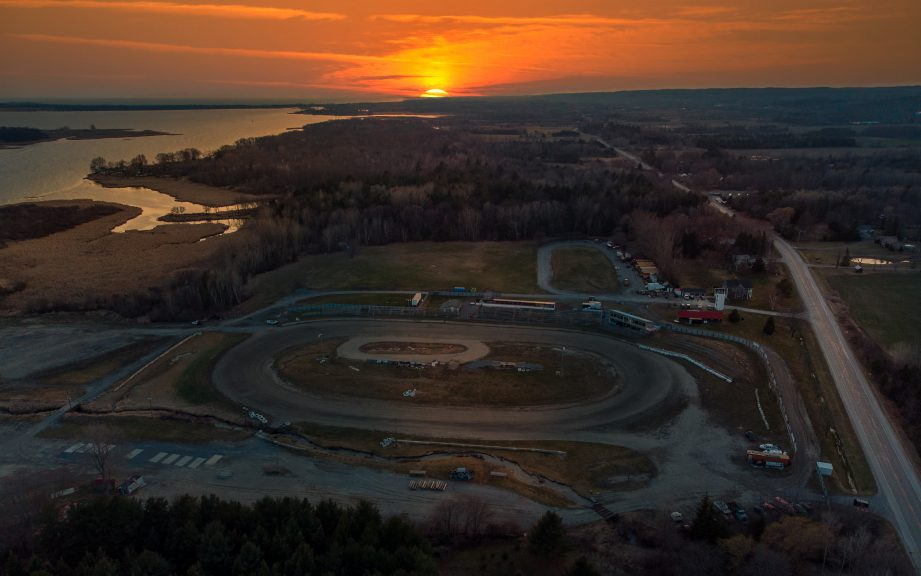 Aerial photo of a race track with a sunrise in the background.