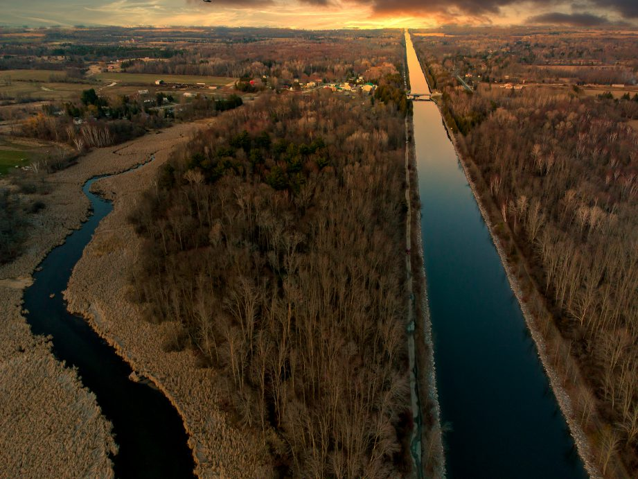 An aerial photo of a canal surrounded by trees and countryside at sunrise.