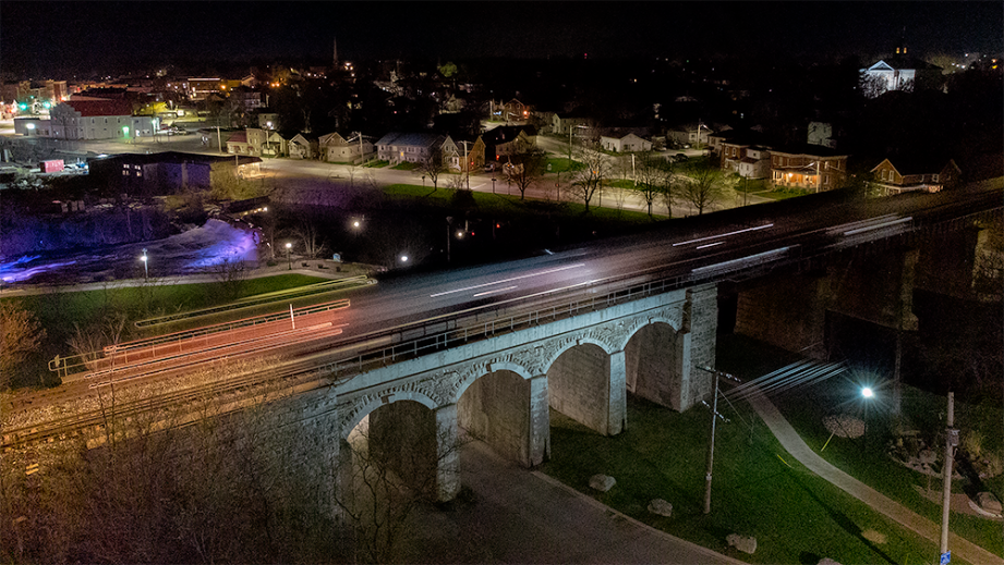 Aerial view of a stone bridge with arches at night, with a starry sky in the background and city lights.