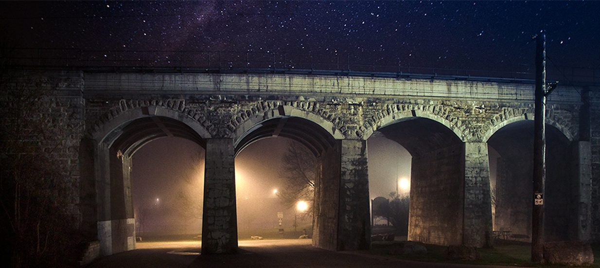 A stone bridge with arches at night, with a starry sky in the background.