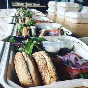 A row of takeout containers with bagels, vegetables and greens.
