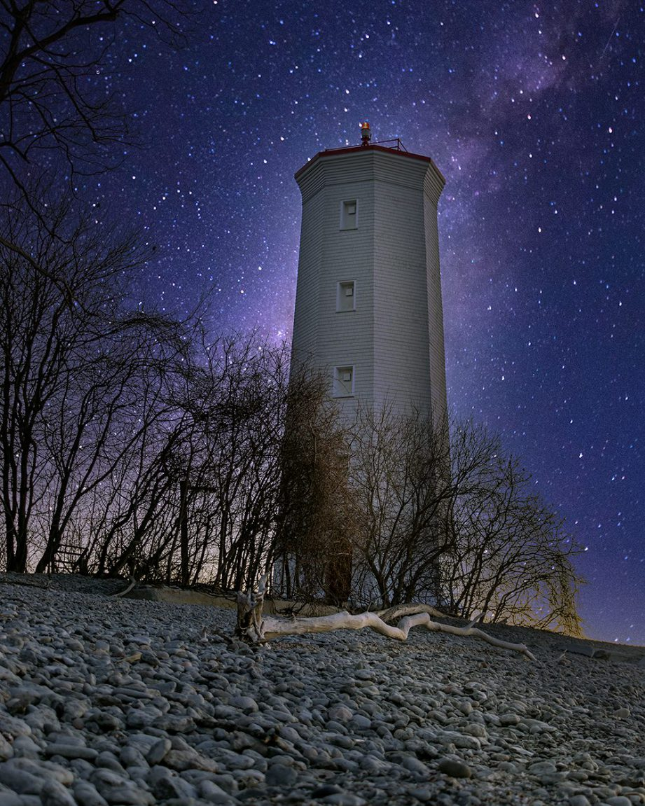 A lighthouse at night, along a stony beach with a starry sky in the background.