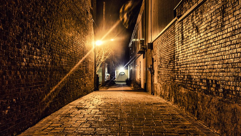 An alley at night, with golden light shining on the walls and footpath.