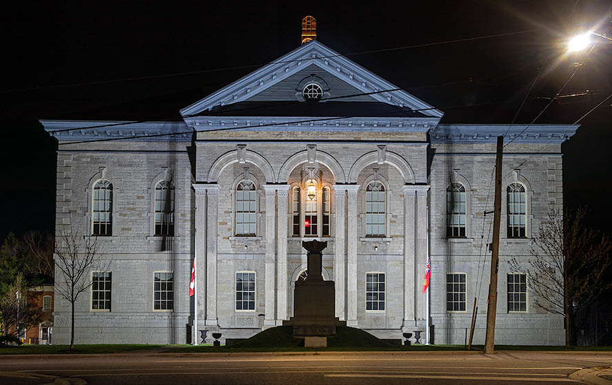 A large white courthouse on a dark evening with a starry sky.