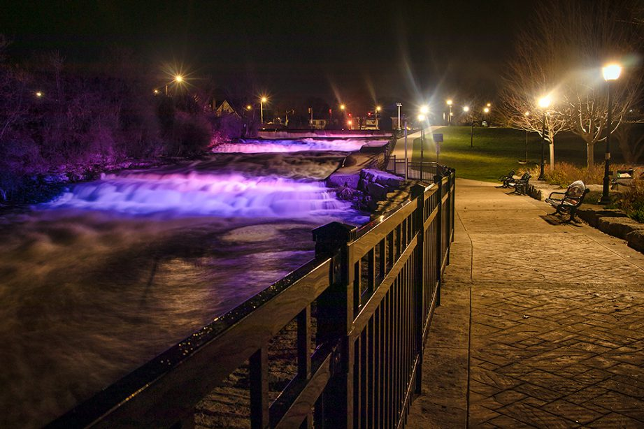 A long exposure of a river flowing, glowing with lights from the city, and a paved path alongside it.