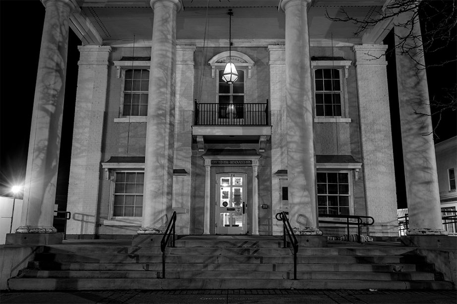 A black and white photo of a white building, Napanee Town Hall, with tall pillars and the front steps leading to the building.