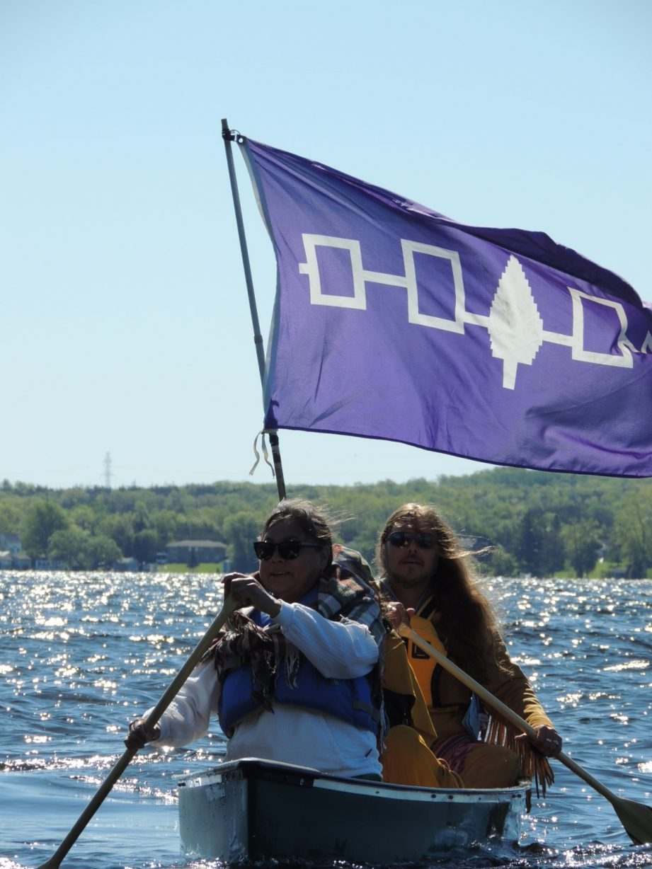 Two people in a canoe paddling in the water, with the purple Haudenosaunee flag.