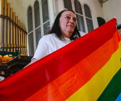 A person wearing a white shirt holding a rainbow flag in a church.