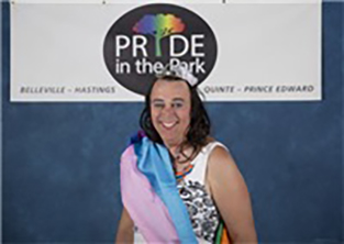 A person wearing a crown and sash, standing in front of a white sign with text: PRIDE in the Park.