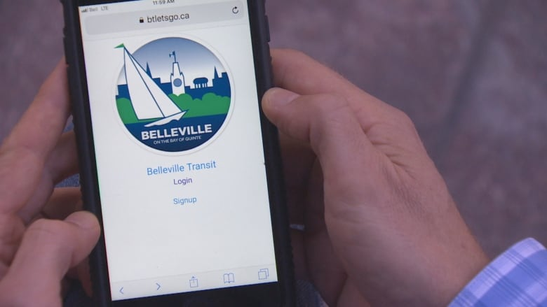 Two hands holding a phone. On the screen there is a white background, logo for the City of Belleville and text below: Belleville Transit, log in or sign up.