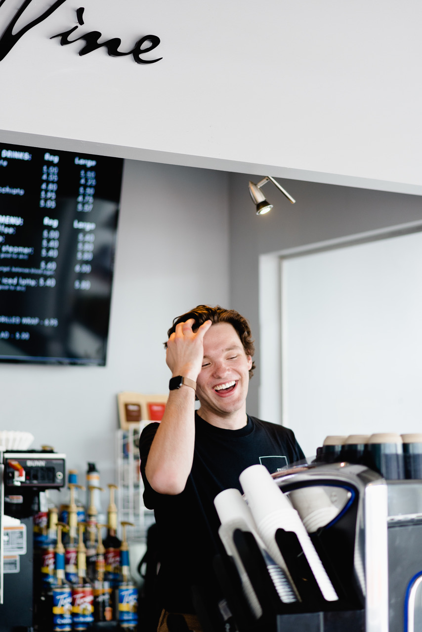 A person standing behind the counter at a cafe, laughing and running a hand through his hair.