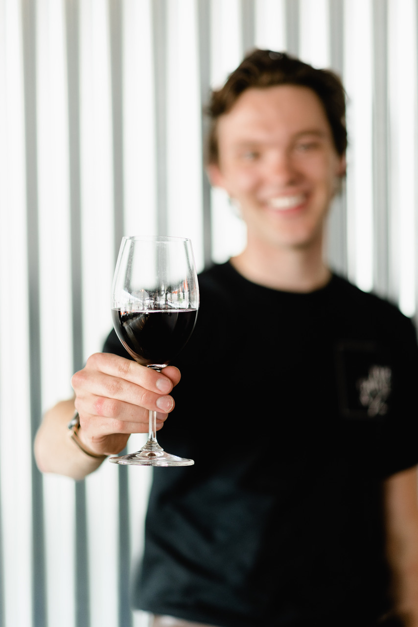 A blurred photo of a person wearing a black shirt, holding a wine glass which is in focus.