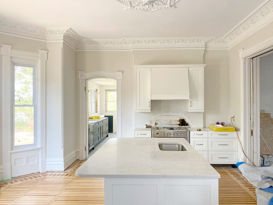 A partially renovated kitchen with wood floors and white fixtures.
