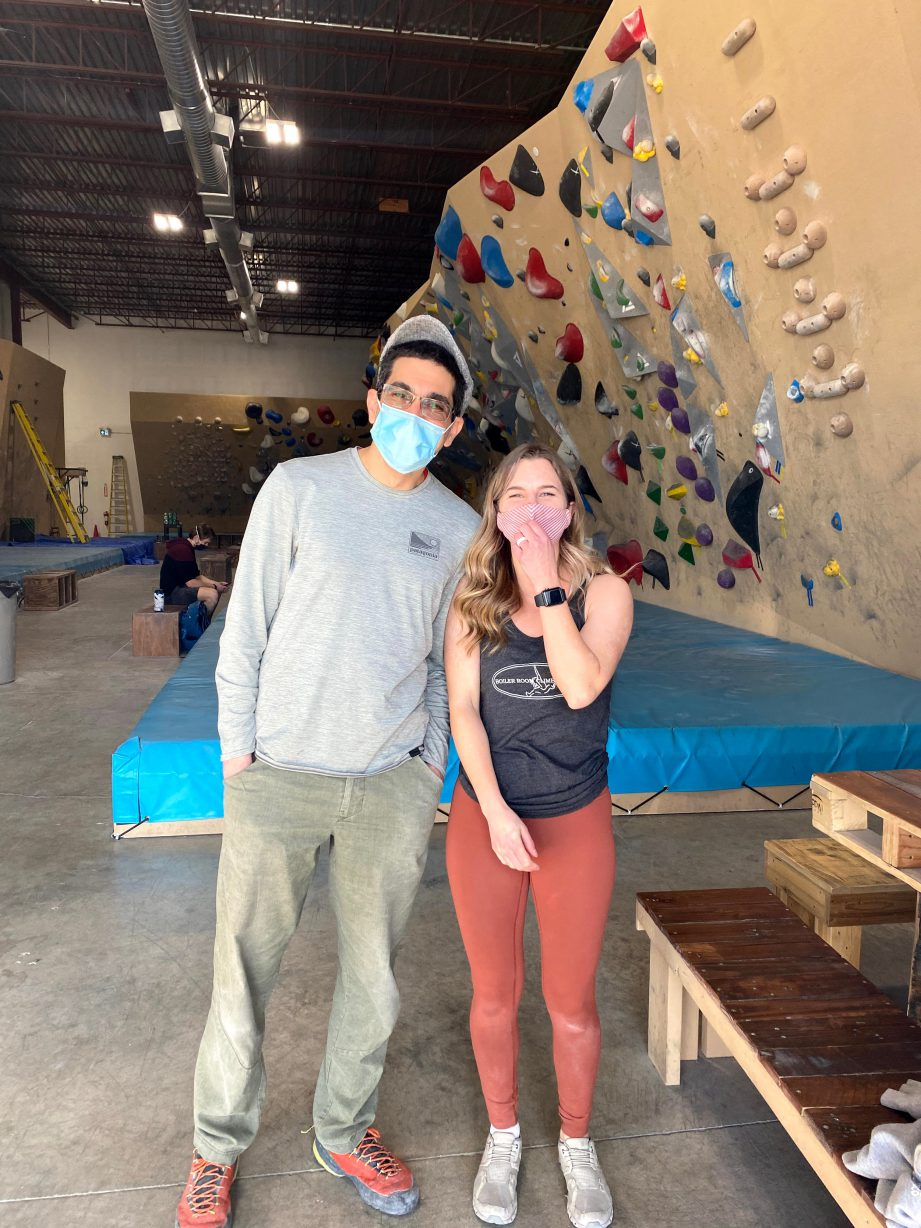 Two people wearing masks standing next to each other in a climbing gym.