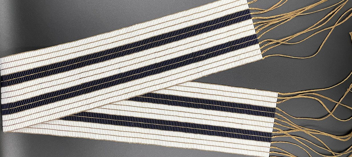 A two row wampum belt, made of white and purple beads, folded in half.