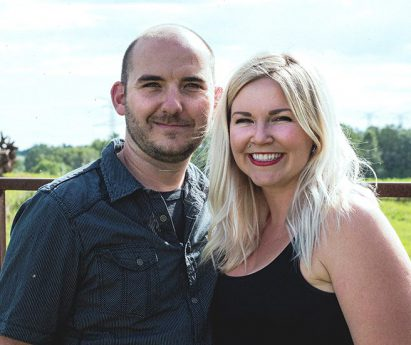 Brad and Rachel Gibson, farmers and owners of Opoma Farms in Quinte West, standing side by side in front of a field.