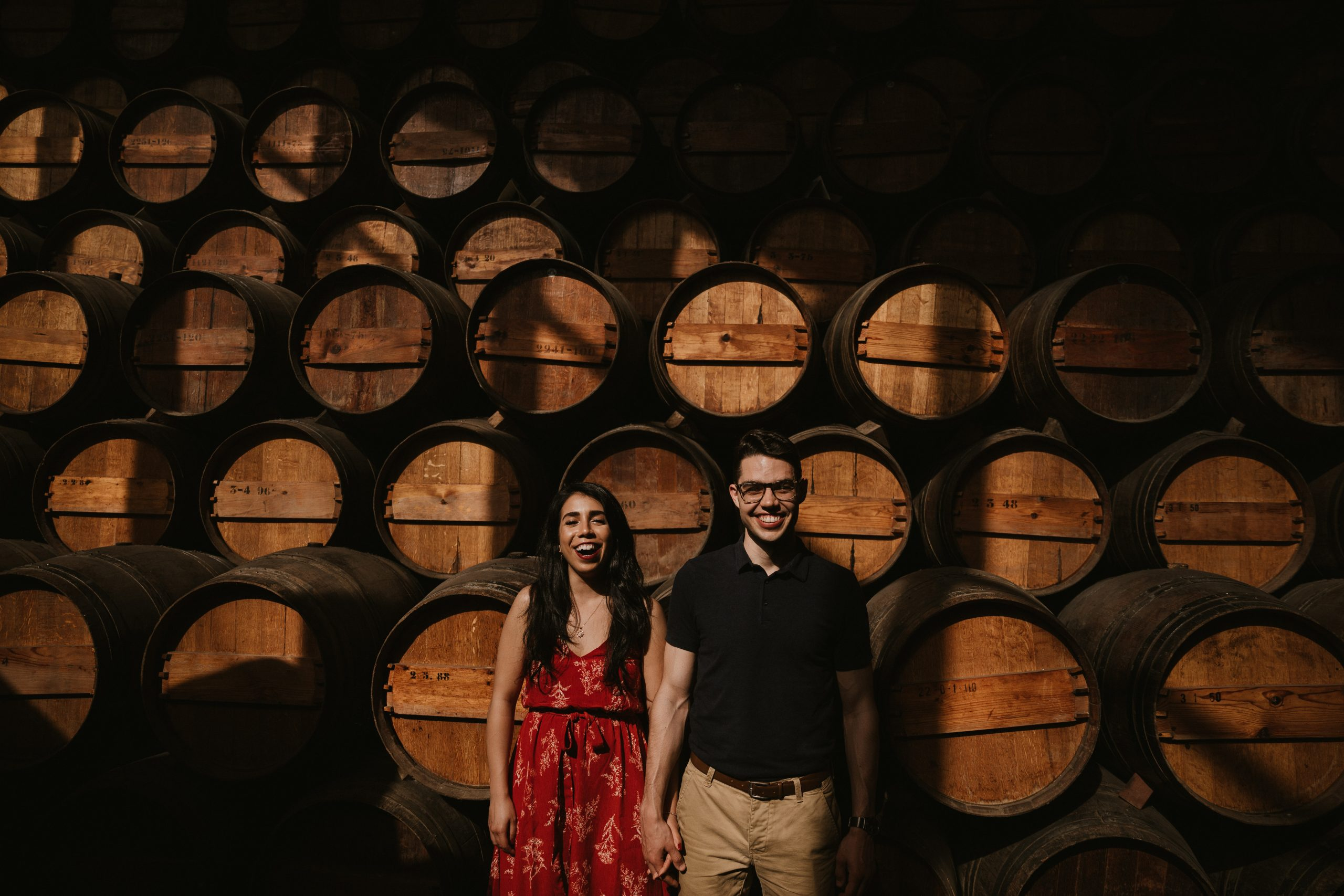Alex and Meghan Callisto, owners of The Cottage by Callisto, standing side-by-side holding hands with wine barrels in the background.
