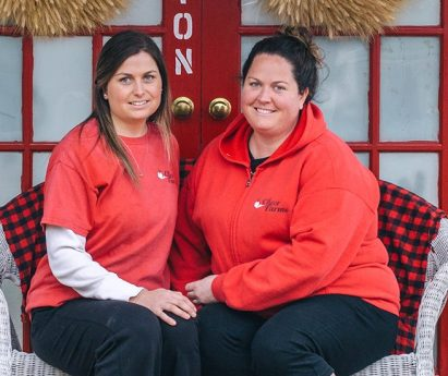 Two staff from Cheer Farms wearing red shirts and black pants, sitting on a bench in front of a red door.