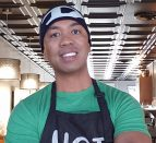A person wearing a green shirt and black apron standing in a cafe.