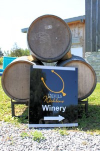 Devils Wishbone Winery sign leaning against three wine barrels.