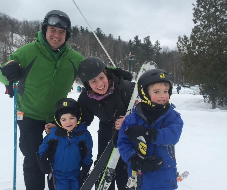 Picture of a smiling family in ski gear holding skiis.
