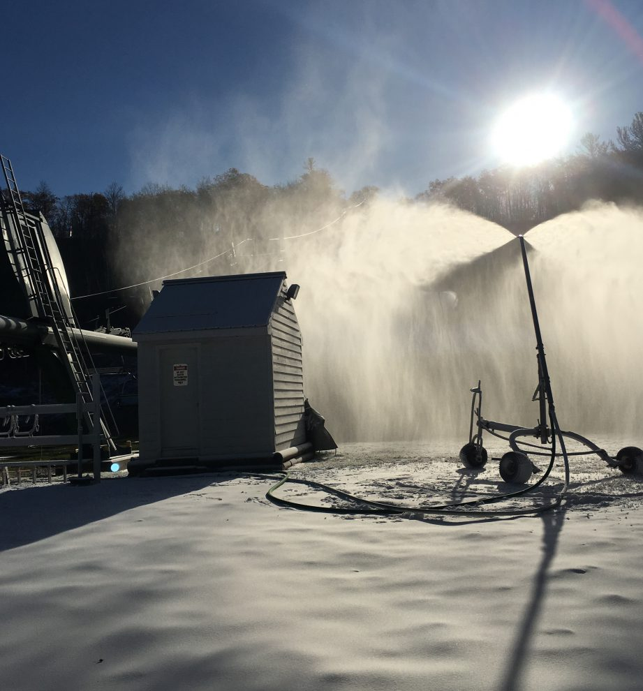 Picture of a snow making machine blowing snow onto the hill.