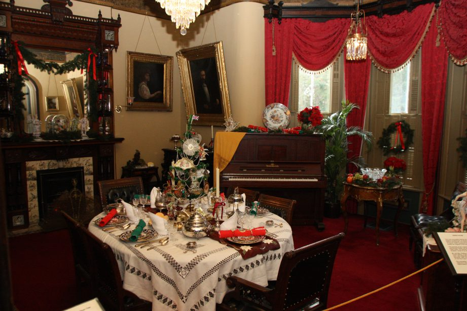 The dining room decorated for Christmas with red and greenery throughout.
