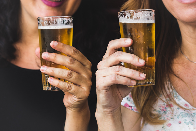 Two women holding up half pints of cold beer in glasses cheers style showing that there will be food and drink at the Quinte Home & Lifestyle Show.
