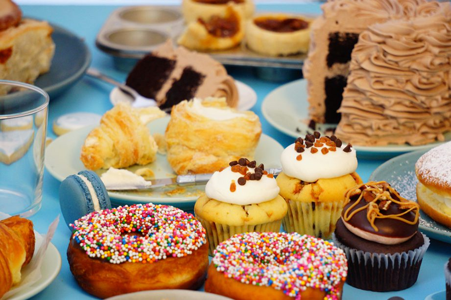 A whole bunch of baked goods like sprinkled donuts, chocolate cake, tarts and cupcakes on a blue table.