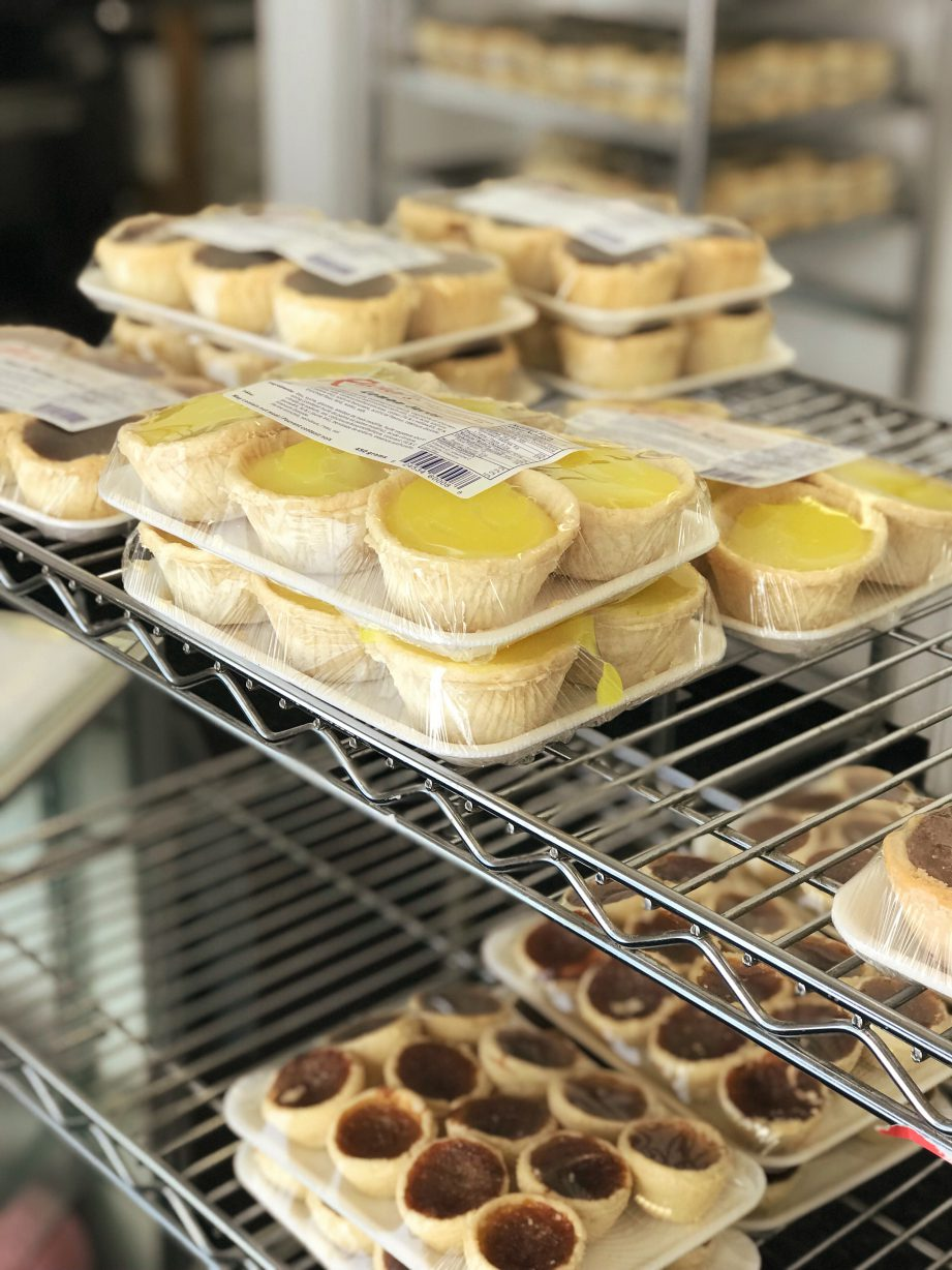 A photo of lemon and butter tarts on a wire shelving unit.