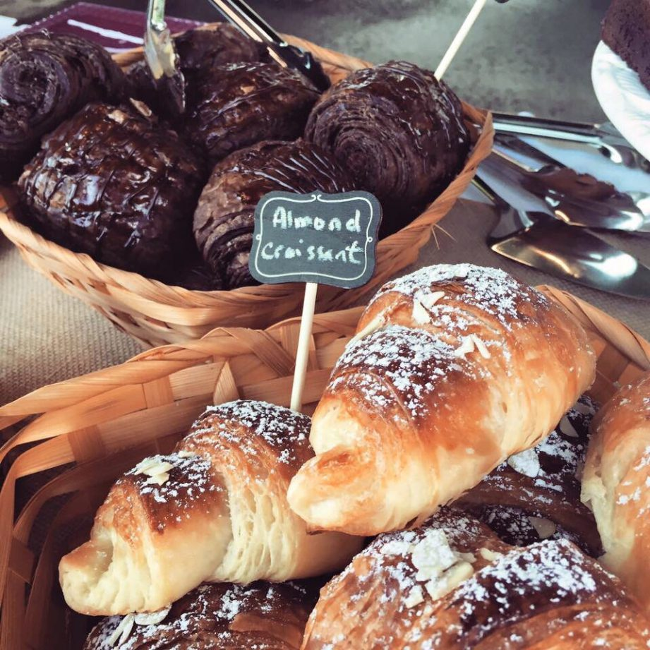 A photo of fresh baked chocolate and almost croissants in wicker baskets.