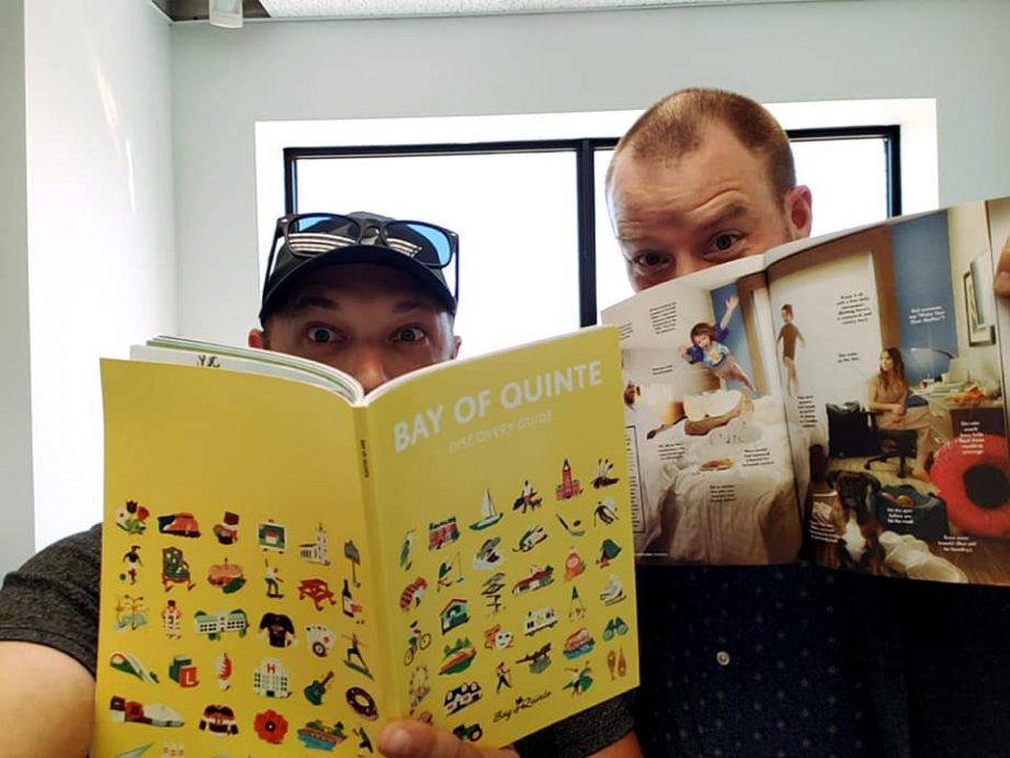 A picture of two men both holding books up to their faces peeking over the top.