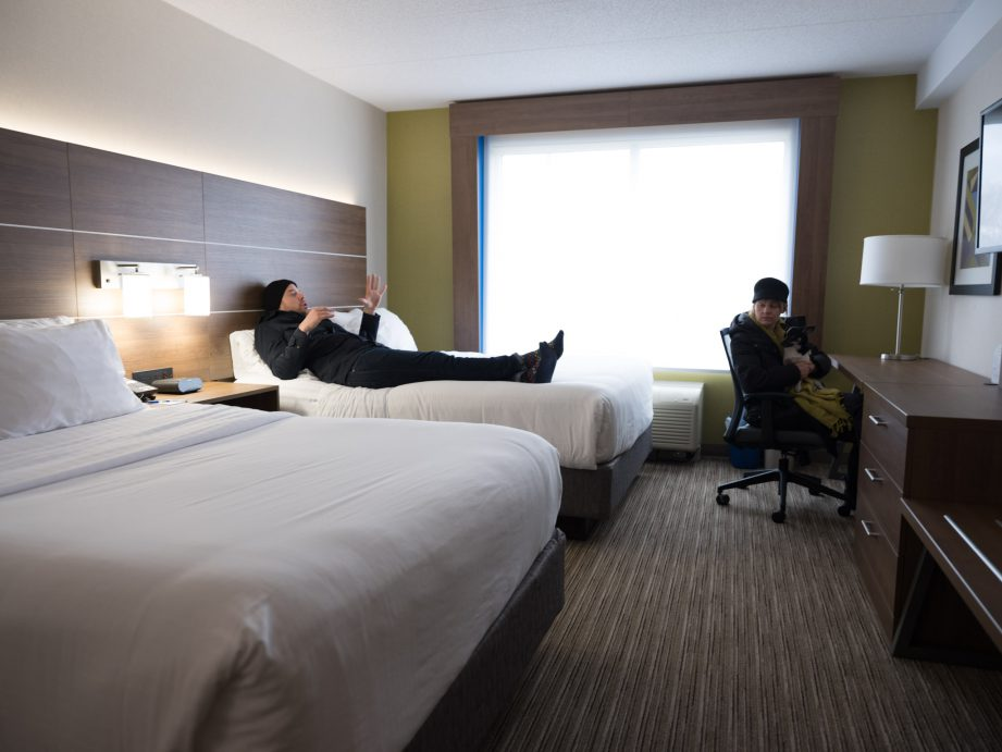 A picture of a hotel room with two beds and a desk. A man is lying on the bed with his hand up in the air and a woman is sitting in a chair at the desk with a dog on her lap.