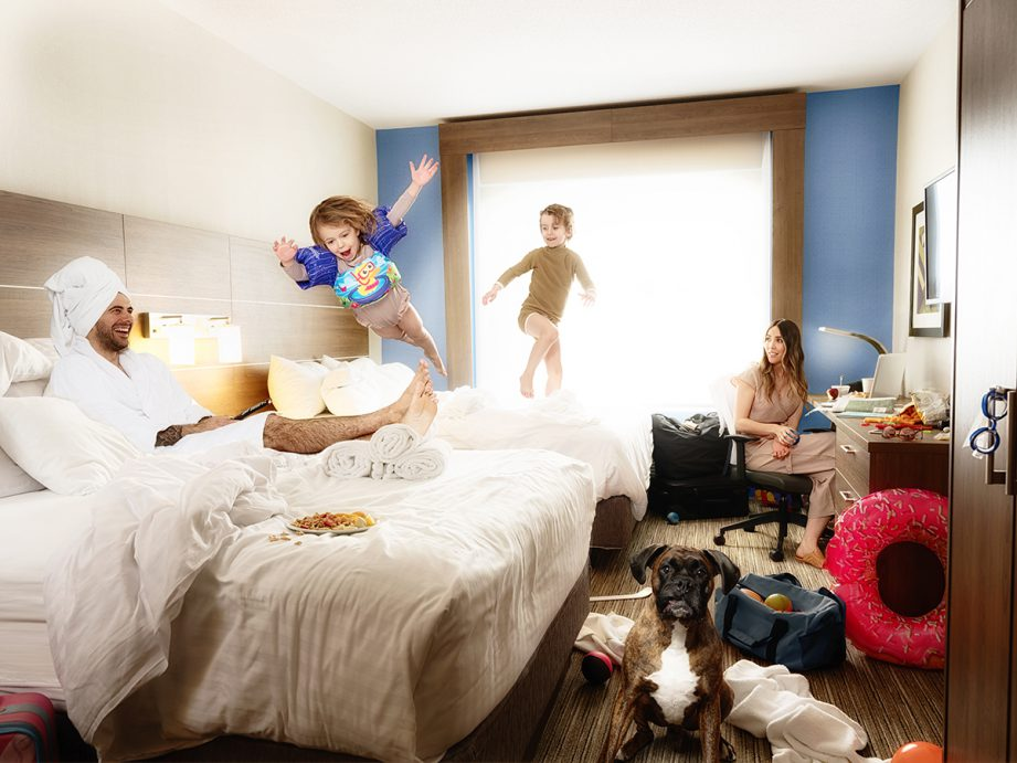 A picture of family in a hotel room. Dad is lying on the bed in towels, daughter is flying through the air from one bed to the other, son is about to jump off the bed and mom is sitting pretty at the desk watching it all unfold.