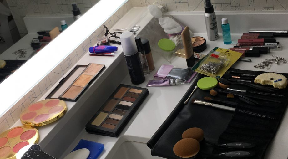 A picture of makeup set out on a bathroom vanity.