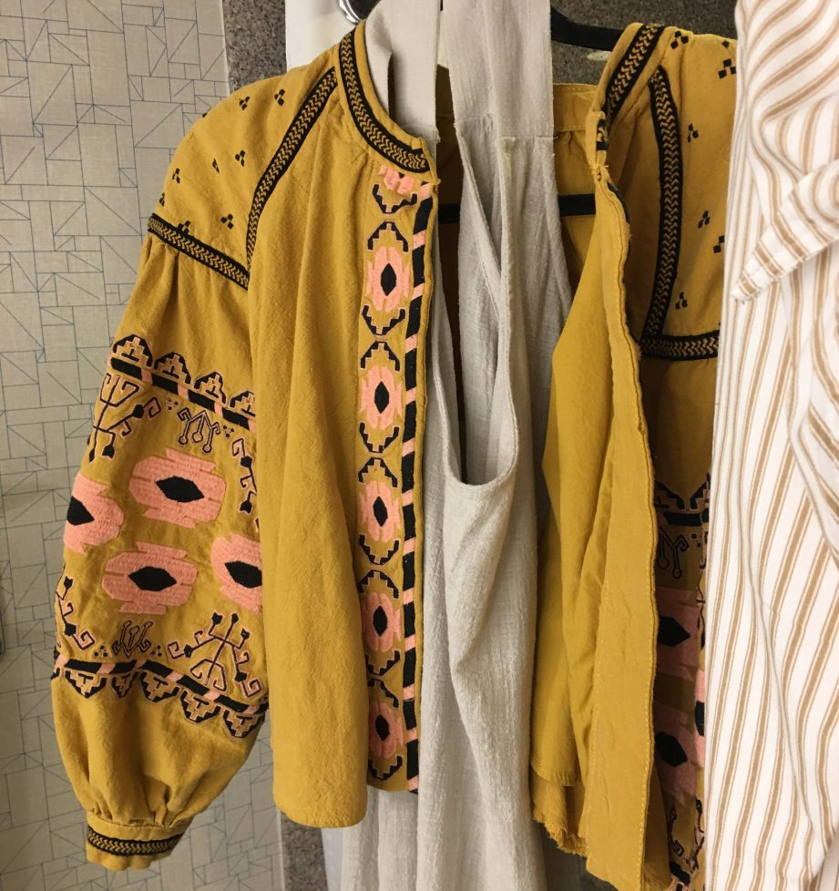 A picture of a mustard coloured jacket with black and peach embroidery.
