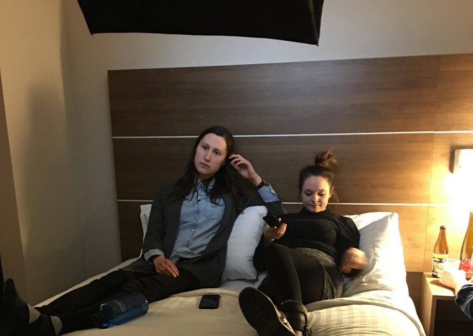 A picture of two women sitting on a bed.