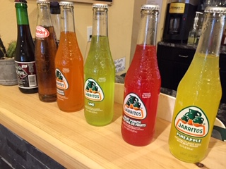 A lineup of Jarritos soda bottles in different flavours.