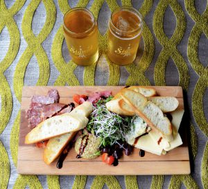 Pints of beer beside a charcuterie board at Birdys Fine Casual Dining