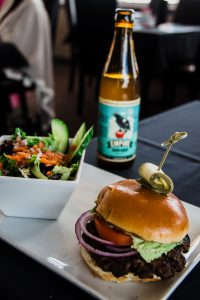 A bottle of Empire Cider, salad and a burger on the table at the Whistling Duck Restaurant.