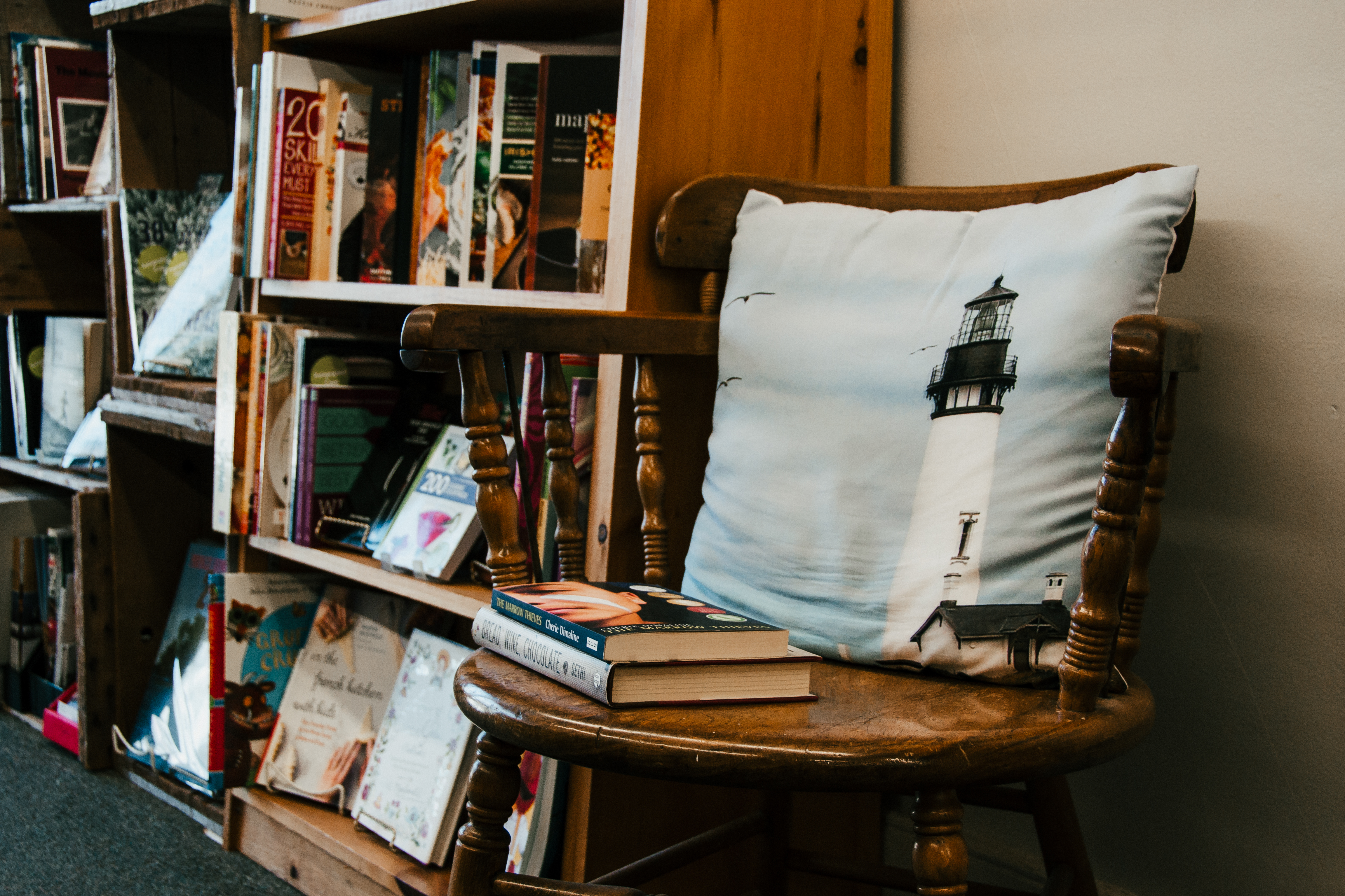 Books and a lighthouse pillow stacked on a chair at Lighthouse Books in Brighton, Ontario.