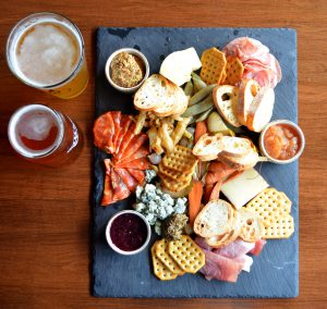 Pints of beer on a table with a charcuterie board at Capers Restaurant.