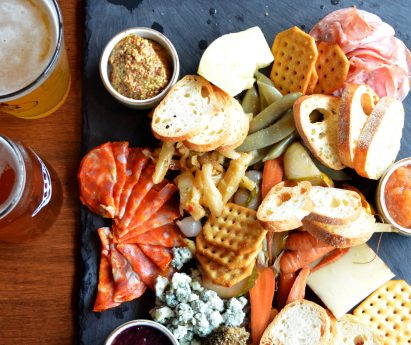 Pints of craft beer on a table with a charcuterie board at Capers Restaurant.
