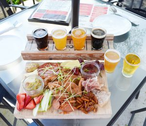 A flight of beer and charcuterie board on a patio table at Signal Brewing Company.