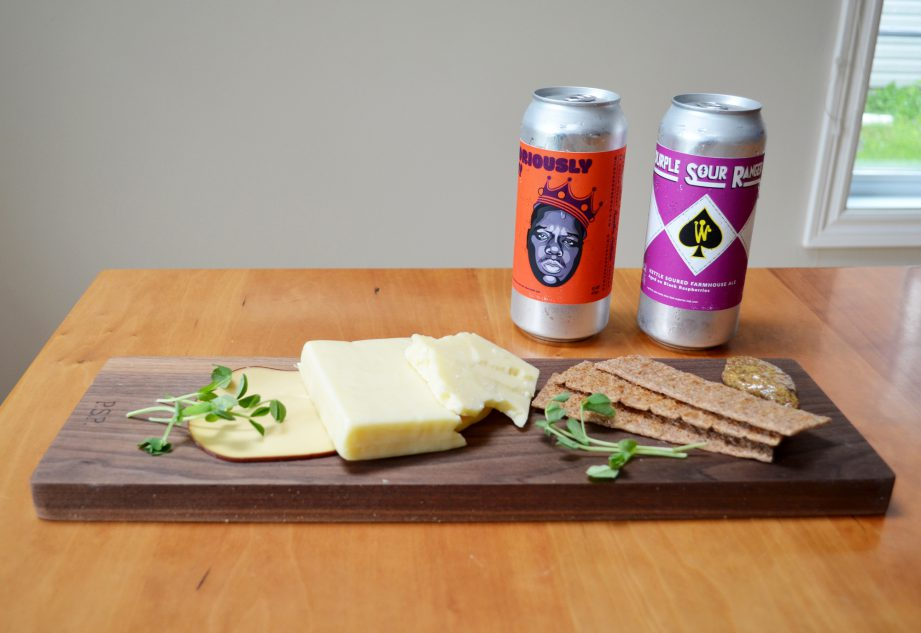 Two cans of beer from Wild Card Brewing Co on a table with a charcuterie board.