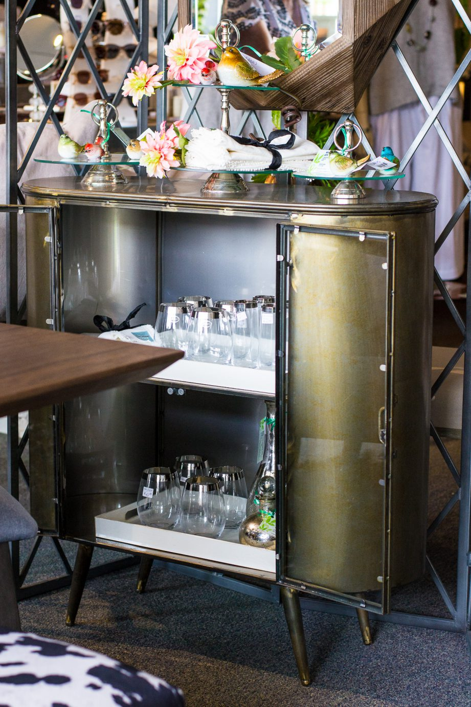 A mid-century shelving unit filled with glassware at Wish Home Accents.
