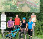 A group of cyclists standing in front of a trails map before mountain biking at Batawa.